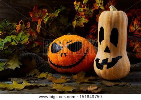 Halloween traditional jack-o-lantern and fall leaves. Halloween symbol smiling pumpkin background.