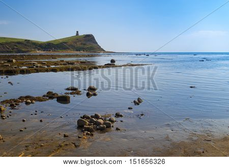Calm waters of Kimmeridge Bay reflect views of Clavell's Tower under blue skies