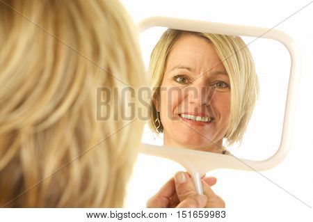 Blonde Woman looking at her refection in a hand held mirror.  Shot from over her shoulder.