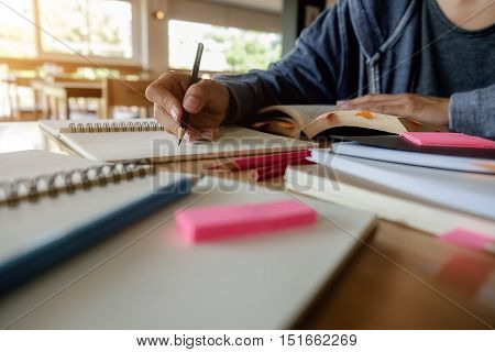 Education concept. Close up of student studies accessories with students discussing their subject on book or textbooks background.
