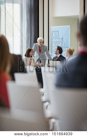 Businesswoman discussing with colleagues during seminar