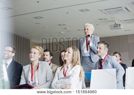 Smiling businesswoman asking questions during seminar