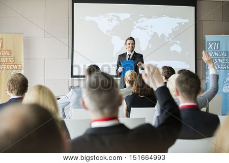 Smiling public speaker asking questions to audience during seminar