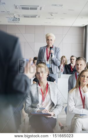 Businesswoman asking questions to public speaker during seminar