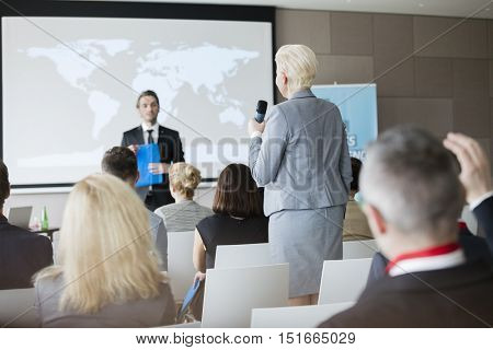 Rear view of businesswoman answering questions during seminar