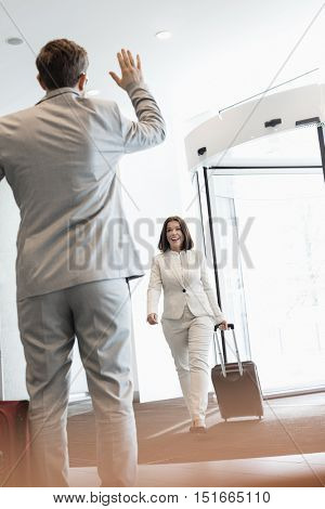 Cheerful businesswoman with luggage walking towards male colleague in convention center