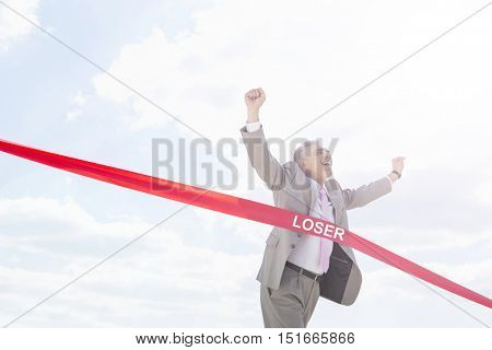 Cheerful businessman crossing red finish line tape against sky with text saying loser