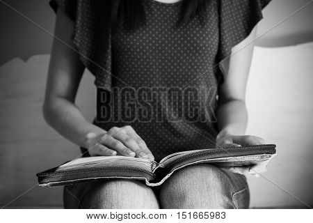 Closeup of a young woman reading a large bible focus on the bible.