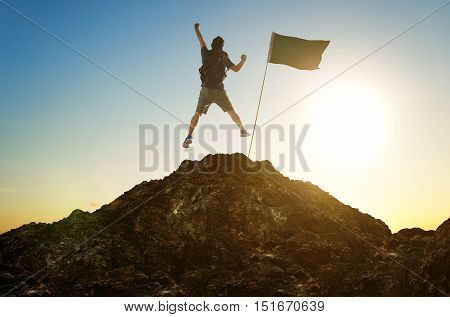 success leadership achievement and people concept - silhouette of young guy with flag on mountain top over sky and sun light background