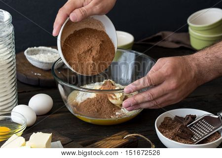 Man cook mixes food ingredients for preparation chocolate dessert on a dark wooden table close up