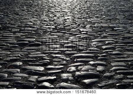 Black cobbled stone road background with reflection of light seen on the road. Black or dark grey stone pavement texture
