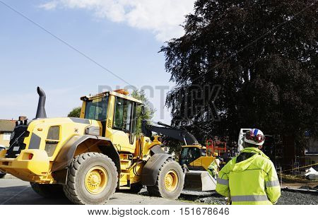 surveyor with measuring instrument, bulldozers and construction site
