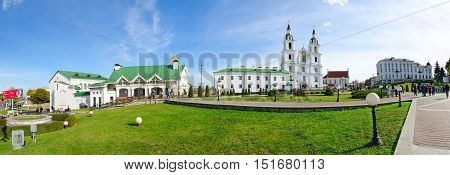 MINSK BELARUS - OCTOBER 1 2016: Panoramic view of Cathedral of Descent of Holy Spirit Monastery of Bernardine temple of St. Cyril of Turov on Nemiga. Unidentified people walk down street on sunny autumn day
