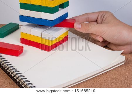 Closeup Hand Boy Take One Block On The Stack Toy Wooden Block. Risk Concepts.