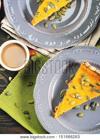 Slice of fall shortcrust pumpkin pie with pumpkin seeds on rustic wooden table with green napkin. Top view. Toned vertical image