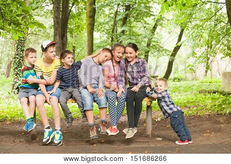 Portrait of beautiful children sitting together on the bench and smiling little boy that push them. Sisyphus metaphor