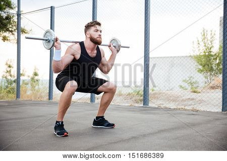 Concentrated bearded sports man doing squatting exercises with barbell outdoors