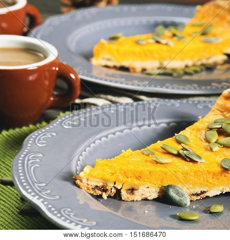 Slice of fall shortcrust pumpkin pie with pumpkin seeds on rustic wooden table with green napkin. Toned square image