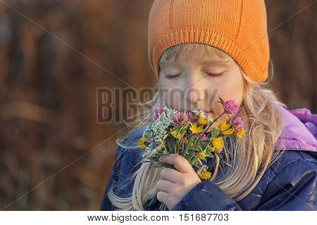 Beautiful blond girl closing her eyes sniffs the bouquet of wildflowers. Autumn.