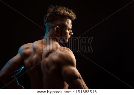 Strong Athletic Fitness Man posing back muscles, triceps, latissimus over black background poster