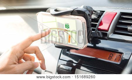 mobile phone and transportation concept - Close up driver hand using navigation or gps on mobile smartphone. Blurred car interior background. Viewing location map in network via smartphone during road trip