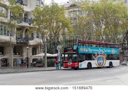 Barcelona, Spain - 24 September 2016: Hop On Hop Off tourist bus at Barcelona. Double decker open air sightseeing coach bus before La Pedrera Casa Mila.