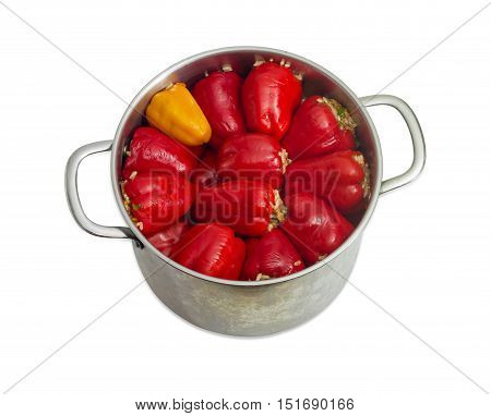 Cooked stuffed red and yellow bell peppers in a large stainless steel saucepan on a light background