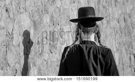 Jew Hasid ethnic headdress. Human shadow on stone wall.