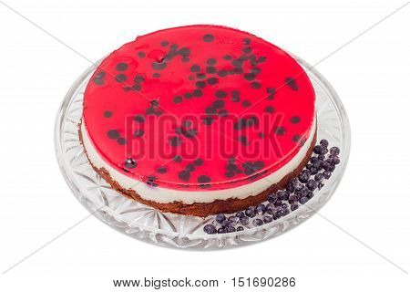 Layered cake with layers of sponge cake milk jelly berry jelly and separately frozen berries on a glass cake serving dish on a light background