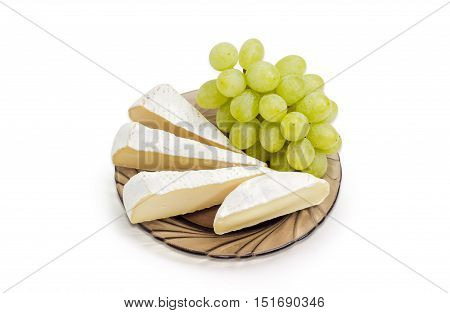 Several slices of Brie cheese and Camembert cheese with cluster of a white table grapes on a dark glass saucer on a light background