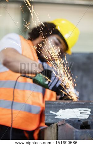 Sparks coming out from grinder with worker in background at metal industry