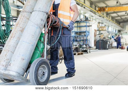 Low section of young manual worker moving gas cylinders in metal industry poster