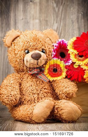 Flowers and a teddy bear on wooden background