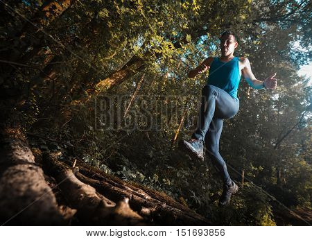 Trail running athlete jumping over wood barrier in the forest