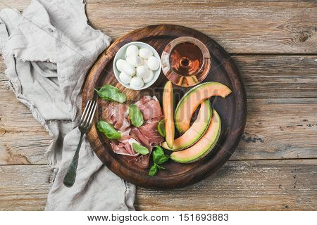 Prosciutto di Parma, cantaloupe melon, mozzarella cheese in bowl, fresh basil leaves and glass of rose wine in round serving tray over rustic wooden background, top view, horizontal composition