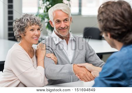 Happy senior couple shaking hands with retirement consultant. Smiling senior man shaking hands with young businessman for business agreement. Handshake between senior man and financial agent.