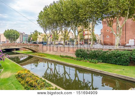 PERPIGNAN,FRANCE - AUGUST 28,2016 - River Bassa near historic building La Castillet in Perpignan. Perpignan is a city a commune and the capital of the Pyrenees Orientales department in south western France.