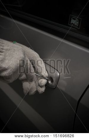 car thief with glove trying to open a vehicle door by screw driver