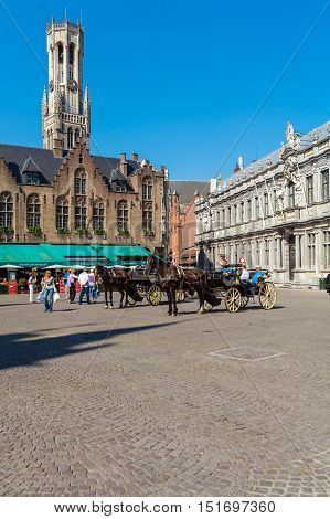 Bruges, Belgium - April 6, 2008: Tourists Ride In Horse-drawn Carriage On The Grote Markt