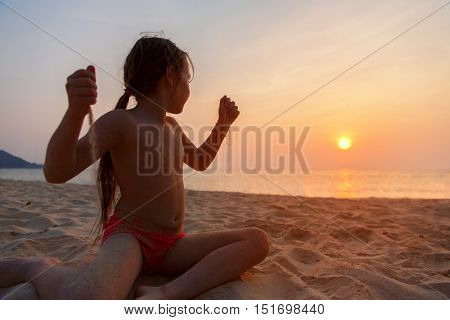 Little girl playing with sand and admiring the sunset