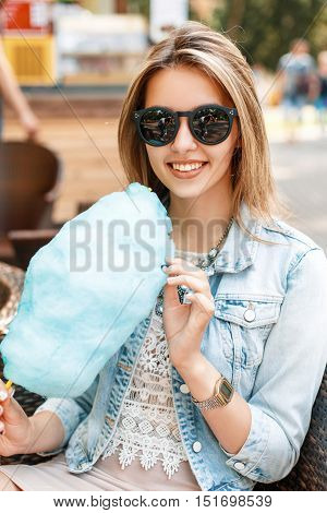 Pretty Woman In Sunglasses And A Denim Jacket Eating Cotton Candy In The Park.