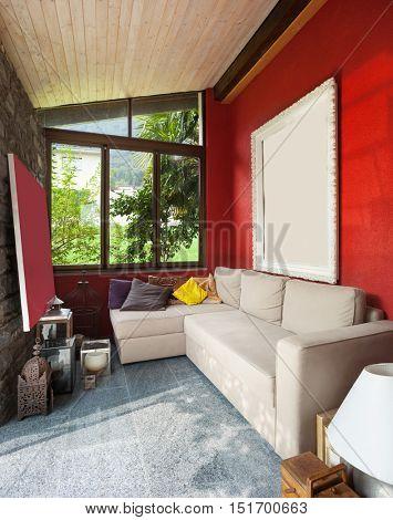Interior, veranda with comfortable divan, red wall