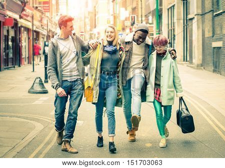 Happy multiracial friends walking on Brick Lane at Shoreditch in London - Friendship concept with multicultural young people on hipster cloths having fun together - Soft focus and desat vintage filter