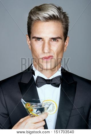 Disgruntled rich man with glass of martini. Photo of stylish man in elegant black suit. High life