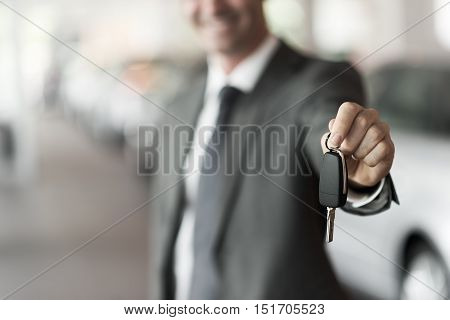 Smiling car salesman handing over your new car keys dealership and sales concept