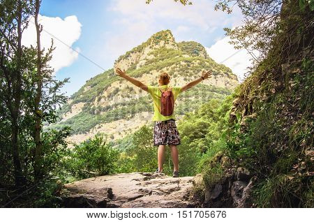 Happy hiker winning reaching life goal freedom and happiness. Winner / Success concept. Men with arms raised in the sky after hiking to mountain top