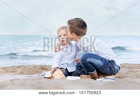 The happy elder brother kisses his  small and cute brother on the beach. Children playing on the beach with sand. Friendship brotherhood concept