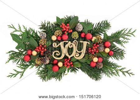 Christmas decoration with gold glitter joy sign, bauble decorations, holly, ivy, snow covered pine cones, cedar cypress and fir leaf sprigs over white background.