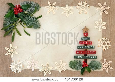 Christmas abstract background border with old wooden tree and snowflake decorations, holly, ivy, mistletoe and snow covered fir on parchment over hemp paper.