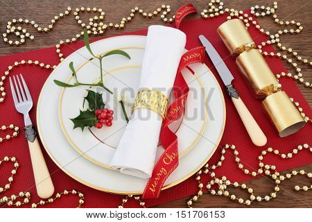 Christmas dinner table setting with white plates, antique cutlery, linen serviette, holly, mistletoe, gold bauble decorations, ribbon and cracker on red place mat over oak background.